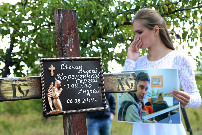 Девушка во время траурной церемонии на месте гибели фотокорреспондента Андрея Стенина