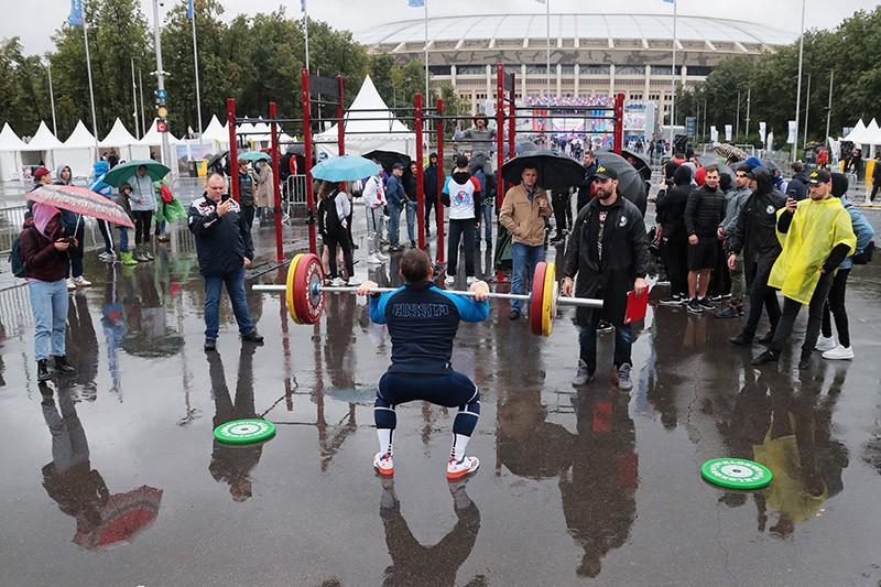Спортсмен поднимает штангу в рамках празднования Дня физкультурника в Москве