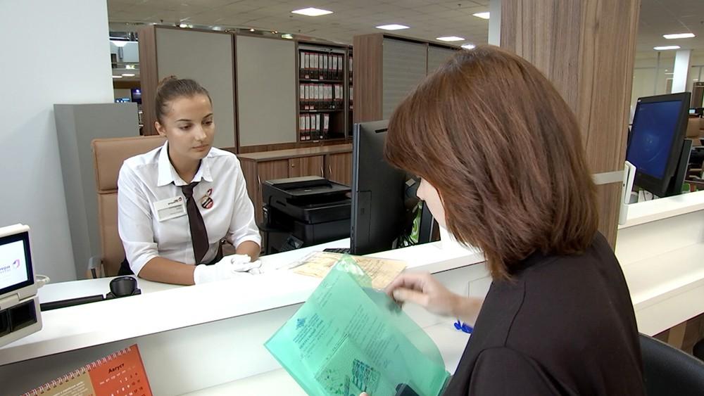 Женщина передает документы в Главархив