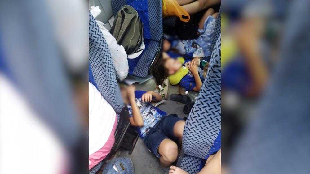 Дети спят на полу в автобусе
