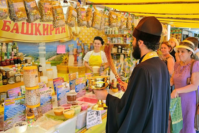 Священник освящает прилавок с медом на ярмарке меда