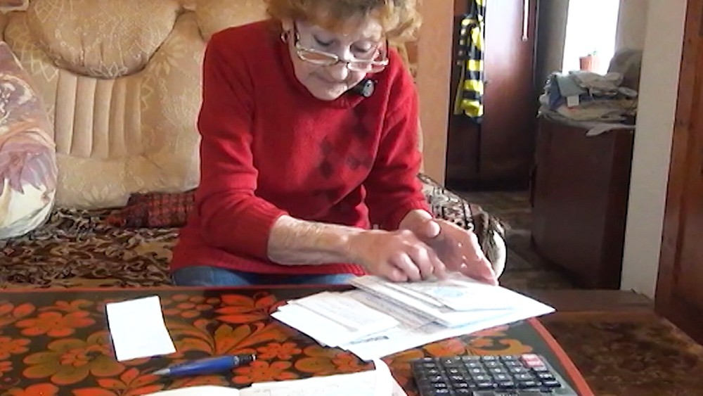 Пенсионерка смотрит на счета