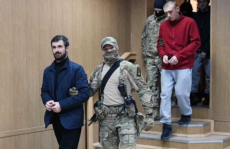 Задержанные украинские моряки в сопровождении конвоя