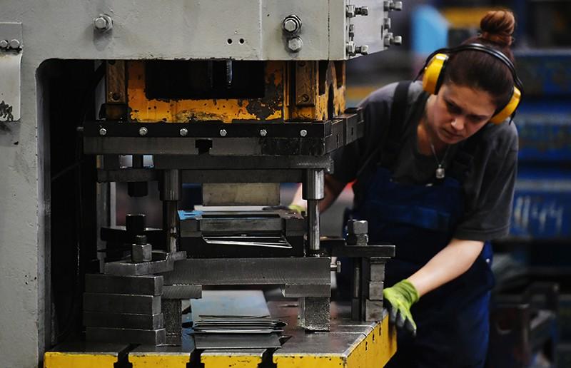 Сотрудница в цехе по производству лифтового оборудования