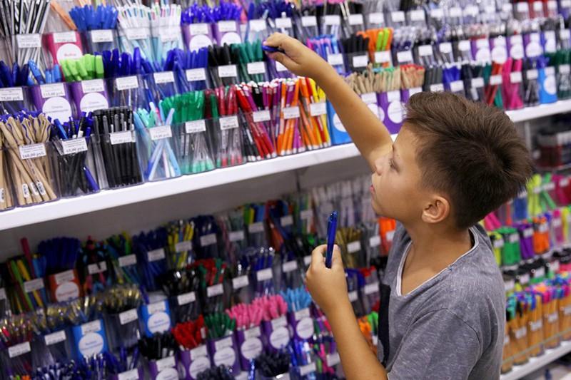 Школьник в магазине канцтоваров выбирает ручку