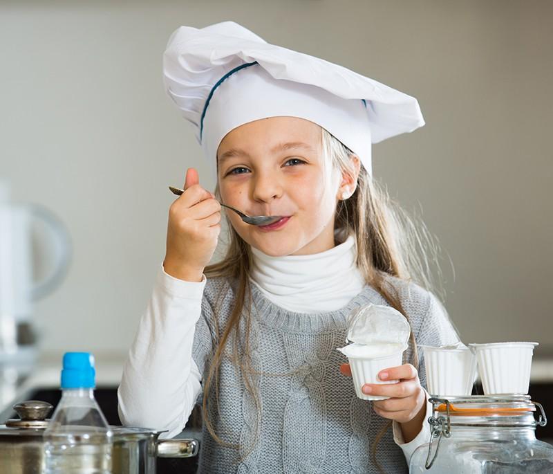 Девочка ест сметану