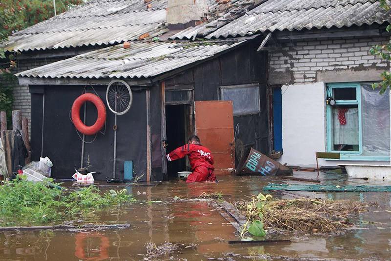 Спасатель МЧС обследует дворы в затопленном паводком поселке