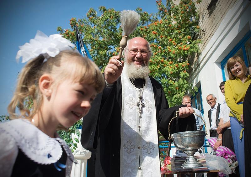 Священнослужитель окропляет святой водой школьников