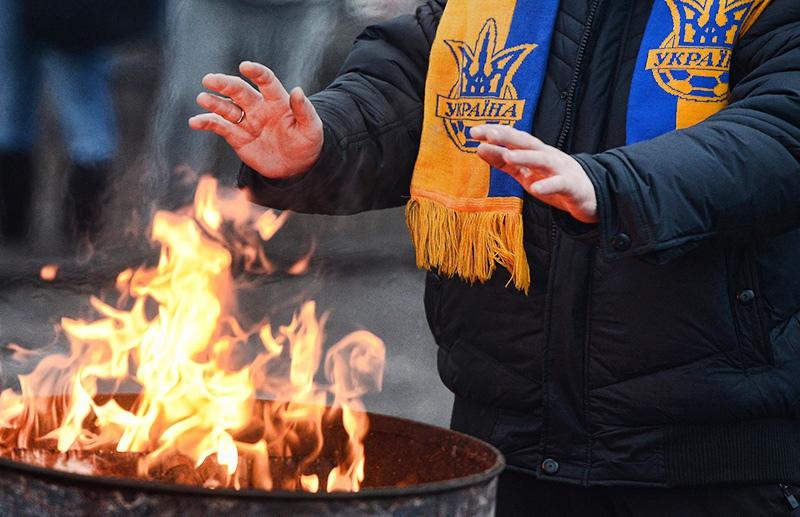 Житель Украины греет руки у огня