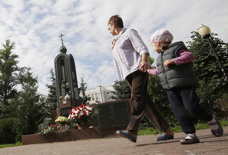 Женщина с ребенком у памятника жертвам террористического акта