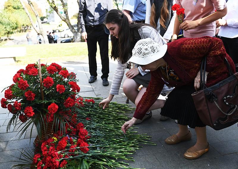 Участники акции возлагают цветы к памятнику жертвам терроризма
