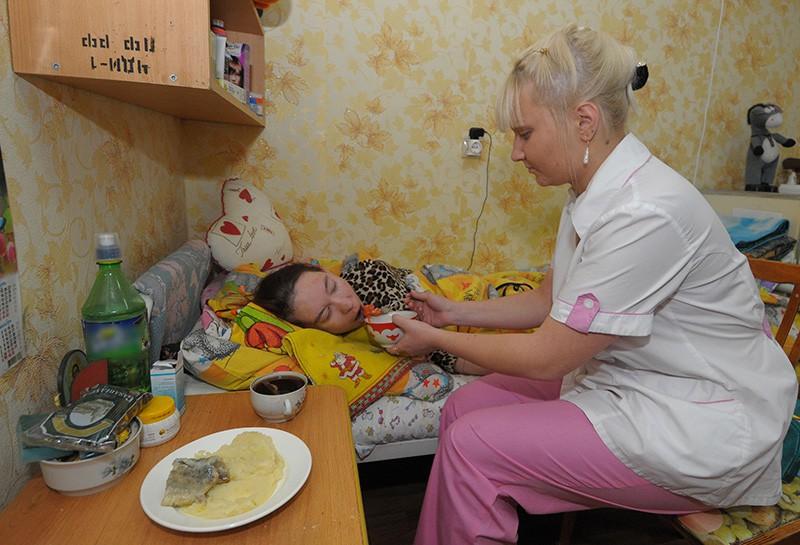 Патронажная сестра кормит лежачего больного