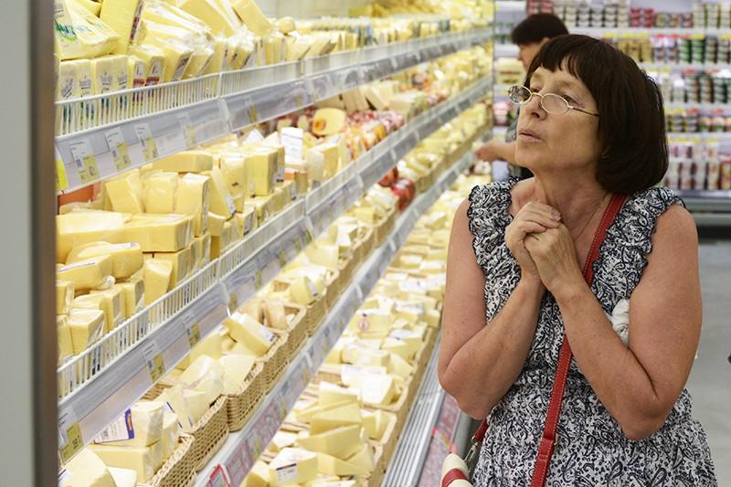 Женщина у прилавка с сырами