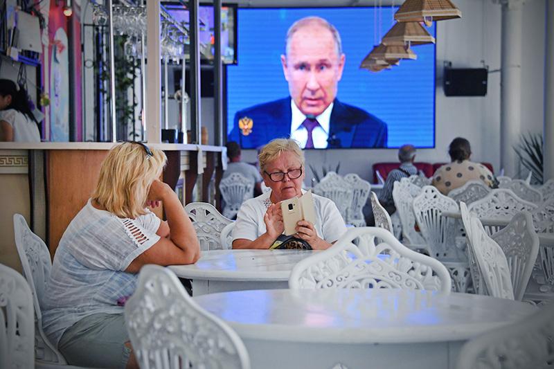 Посетители кафе смотрят трансляцию прямой линии с президентом России Владимиром Путиным