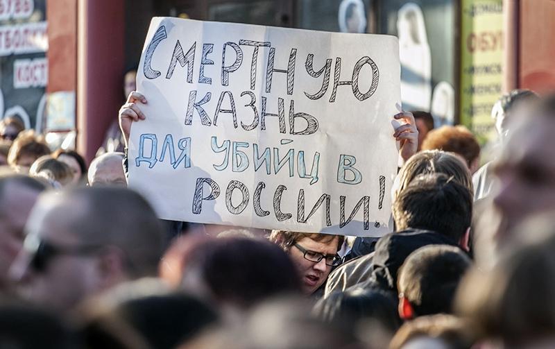 Мужчина с плакатом о требовании казни для виновных в убийствах