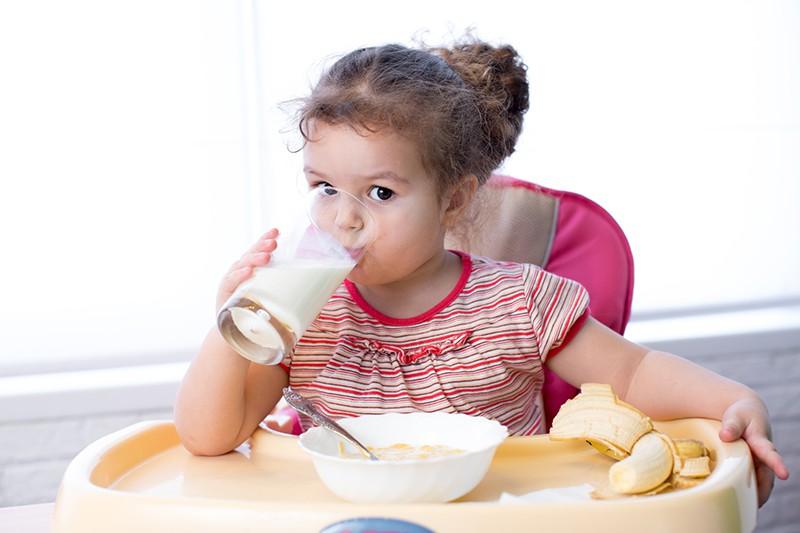 Девочка пьет кефир