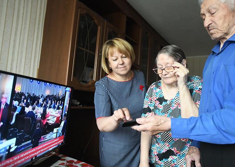 Волонтер помогает пенсионерам настроить прием цифрового телевидения
