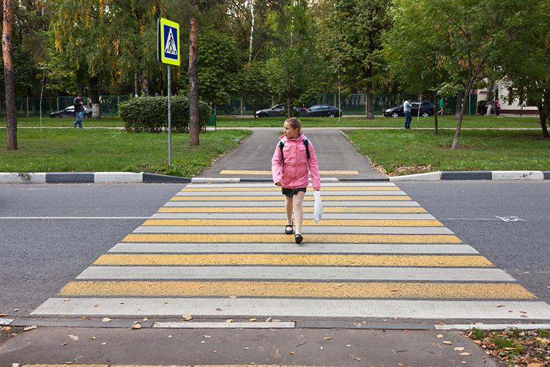 Девочка идет по пешеходному переходу