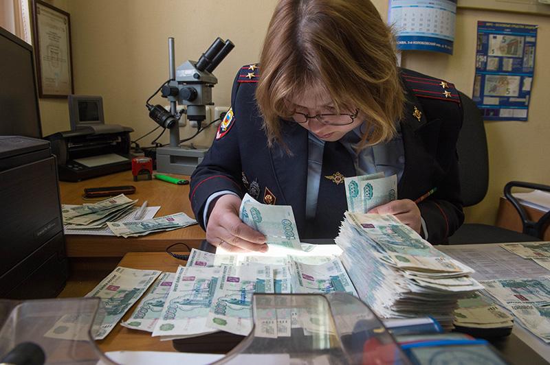 Сотрудник полиции осматривает фальшивые купюры