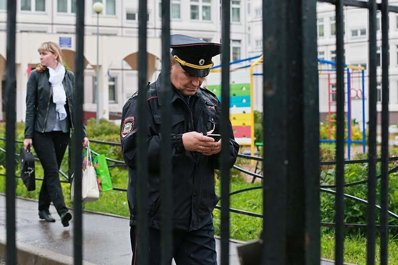 Сотрудник правоохранительных органов у здания школы