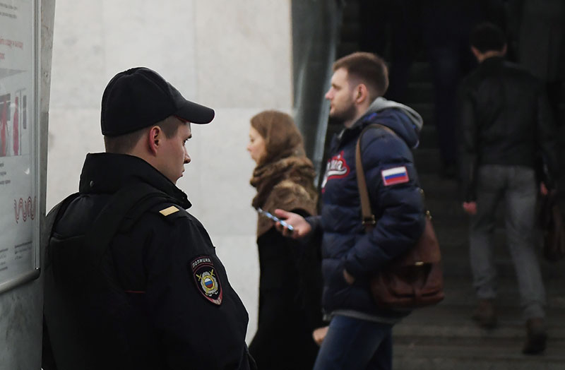 Сотрудник полиции и пассажиры на станции метро в Москве