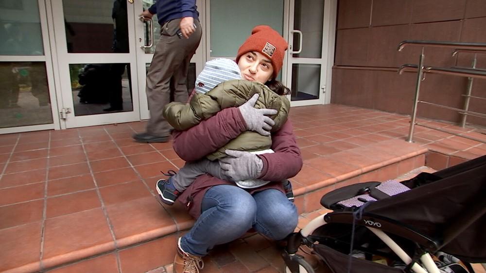 Женщина с ребенком сидит у подъезда дома