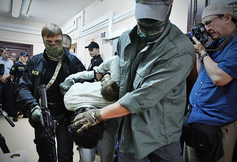 Сотрудники правоохранительных органов ведут арестованного
