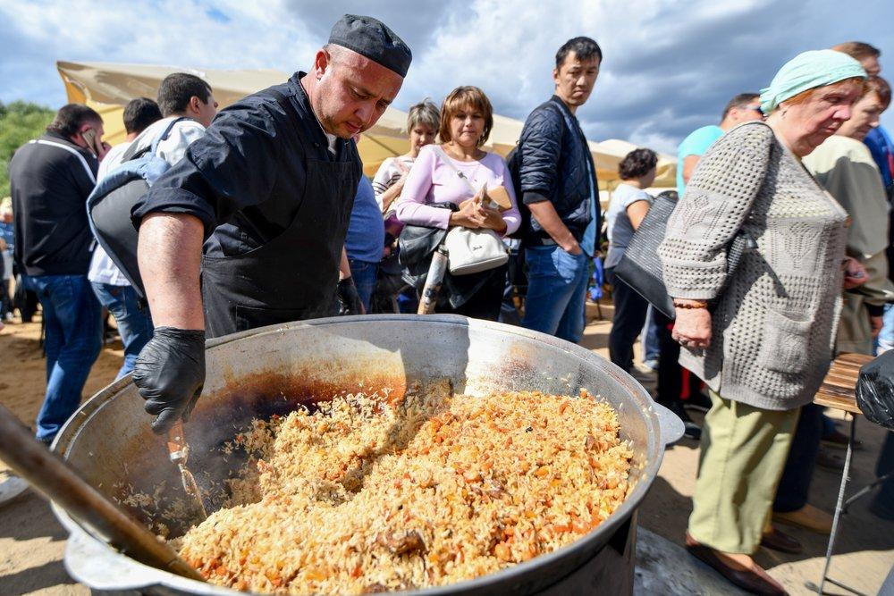 Повар готовит плов на фестивале