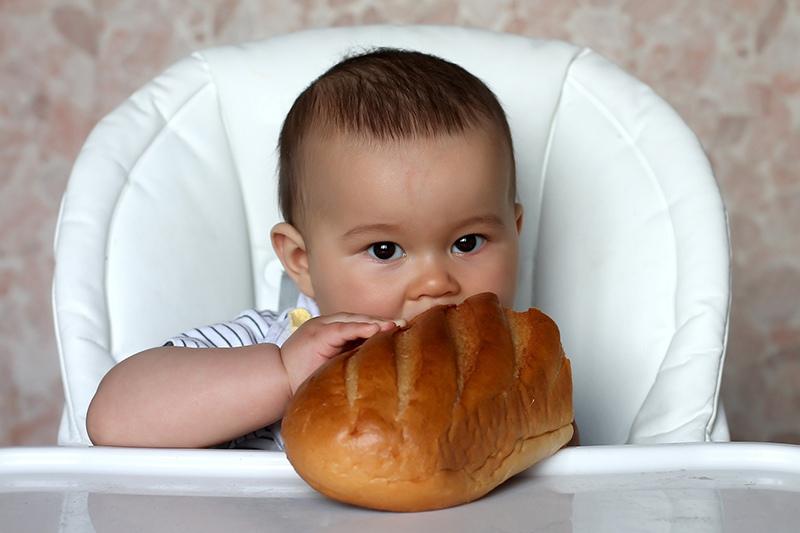 Ребенок с батоном белого хлеба