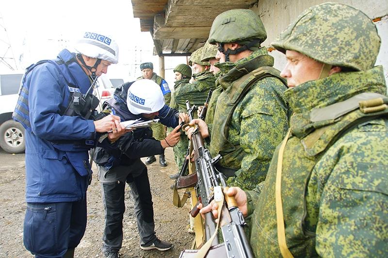 Наблюдатели ОБСЕ (слева) следят за отводом сил бойцов подразделений ЛНР в поселке Золотое в Луганской области