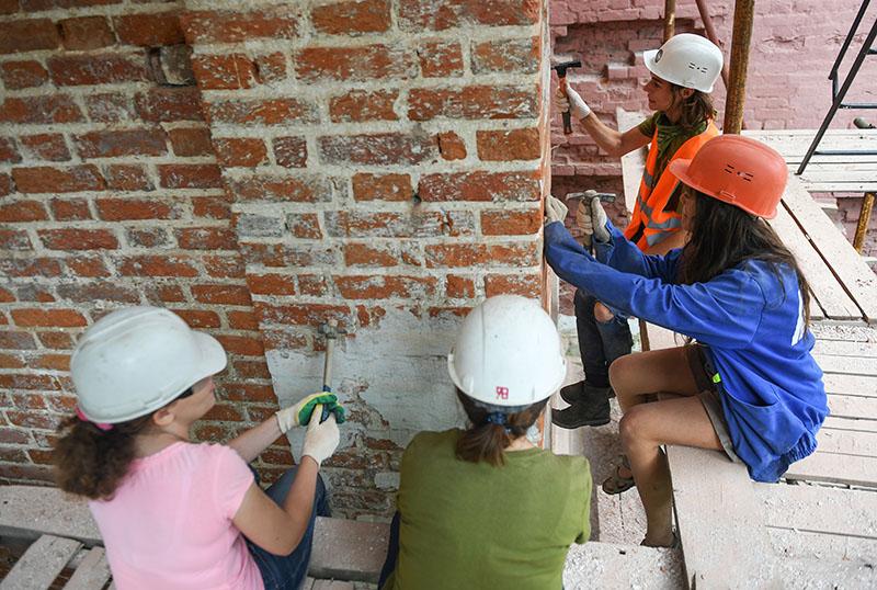 Девушки волонтеры во время реставрации памятника архитектуры