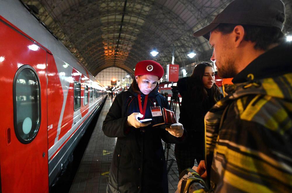 Проводница поезда проверяет билеты пассажира