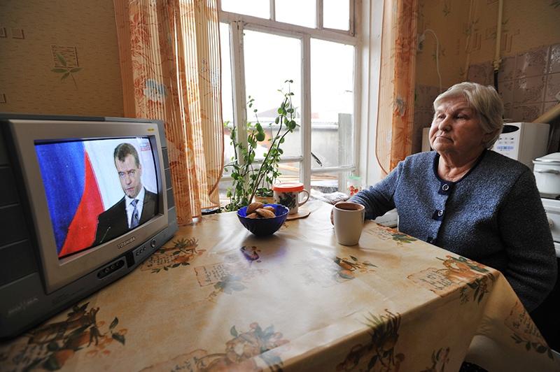 Женщина смотрит телетрансляцию с Дмитрием Медведевым