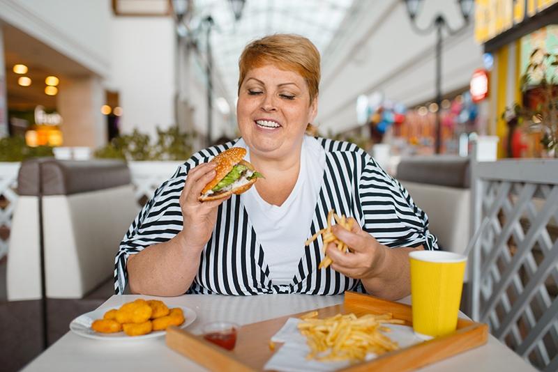 Полная женщина кушает