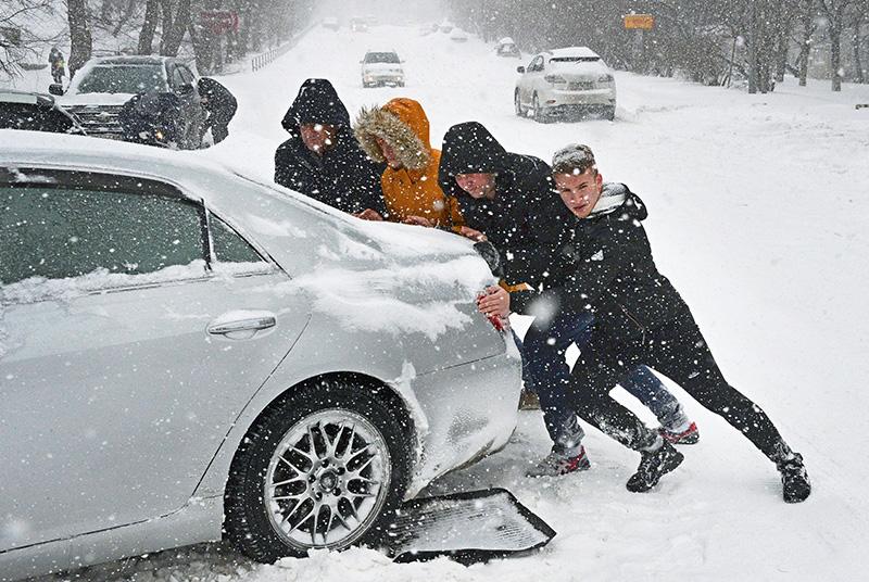 Люди толкают машину на одной из занесенных снегом улиц Владивостока
