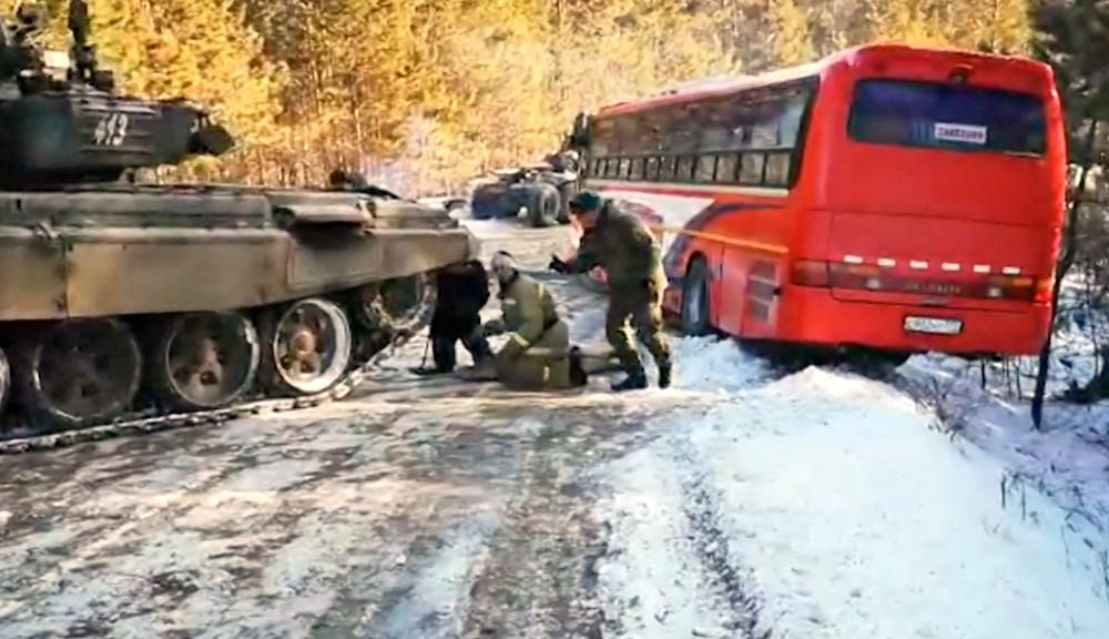 Танк достает из кювета автобус