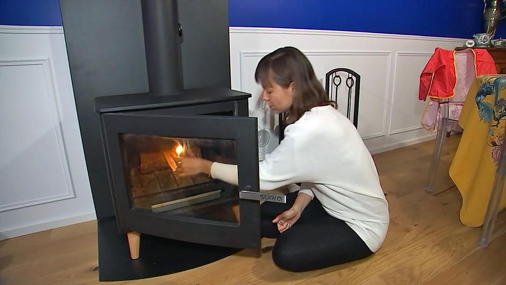Женщина топит печь