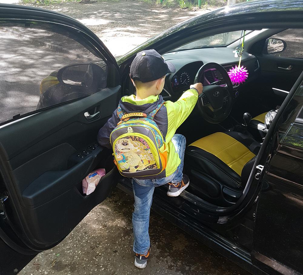 ребенок садится за руль автомобиля