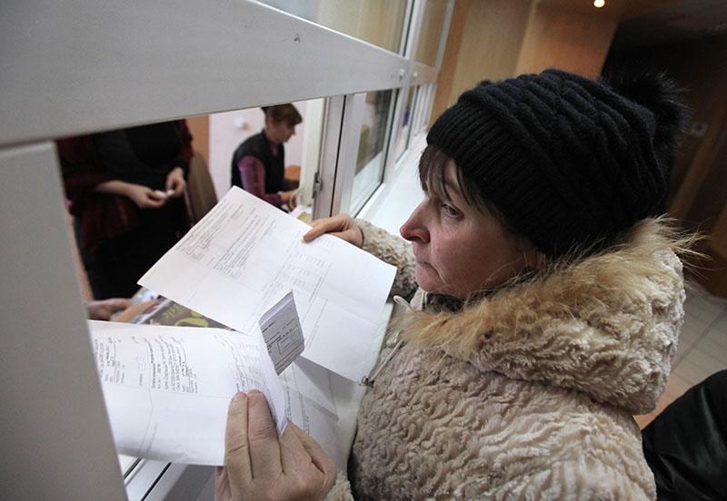 Женщина оплачивает коммунальные услуги