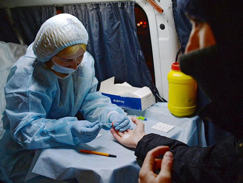 Медицинский работник производит экспресс-анализ крови
