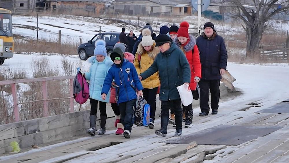 Школьники идут по аварийному мосту