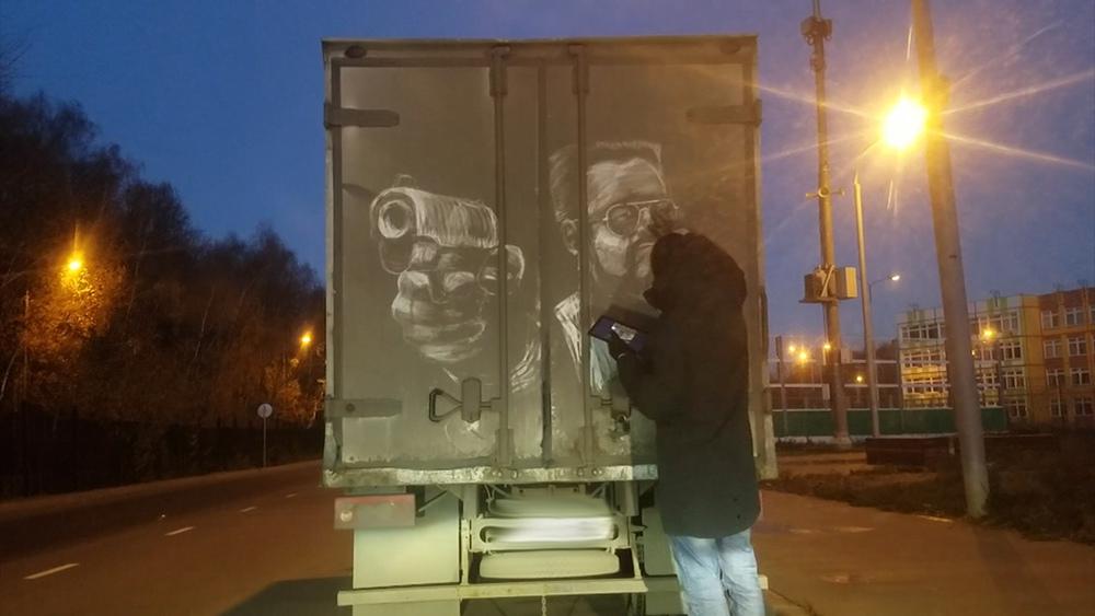 Художник рисует на грязных машинах