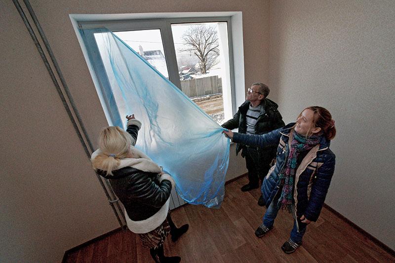Люди осматривают квартиру в новом доме