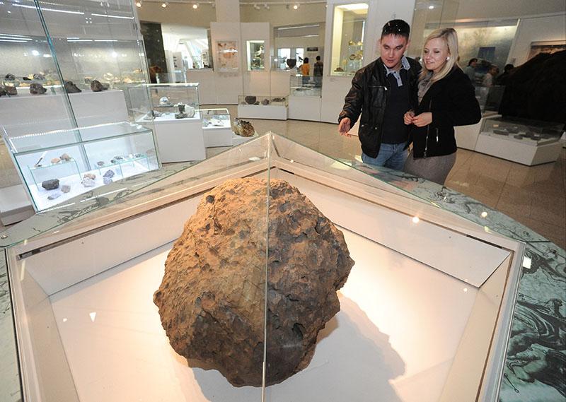 Посетители осматривают метеорит Челябинск в одном из залов краеведческого музея Челябинска