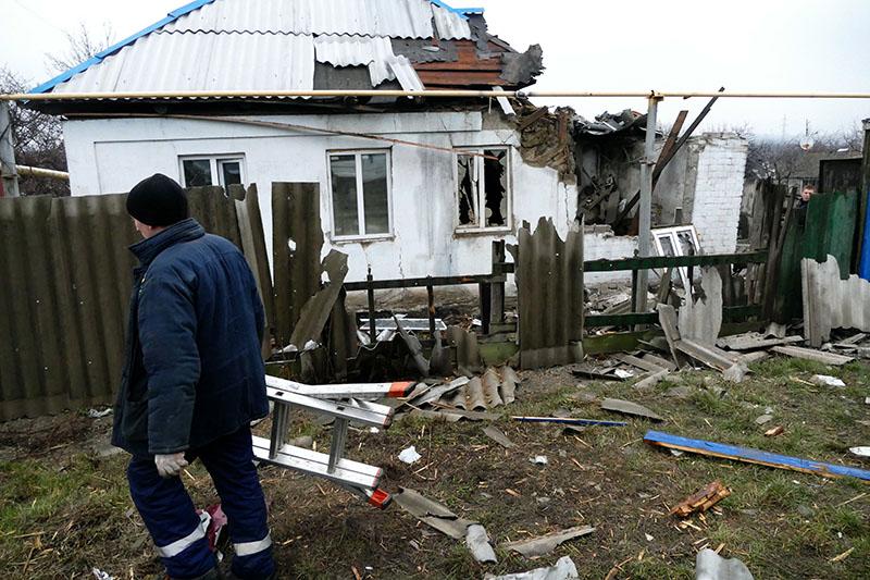 Мужчина у дома, поврежденного в результате обстрела украинскими силовиками