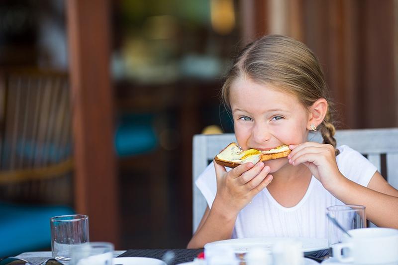 Девочка ест хлеб с маслом