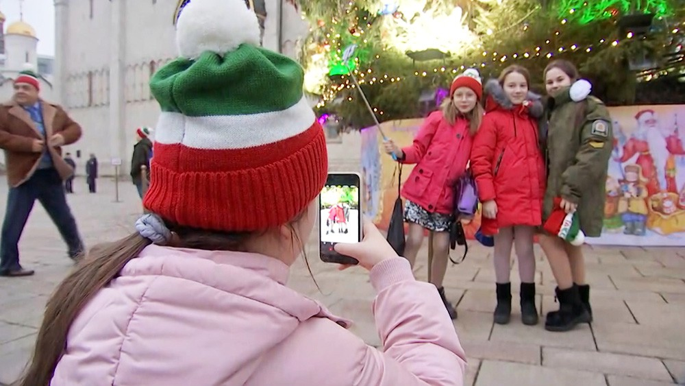 Дети фотографируются у елки