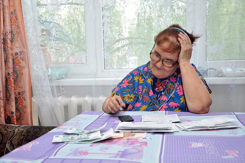 Пожилая женщина оплачивает жкх