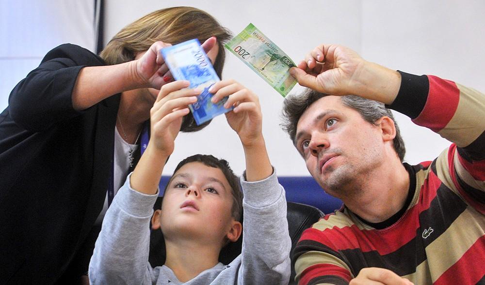 Люди рассматривают рубли