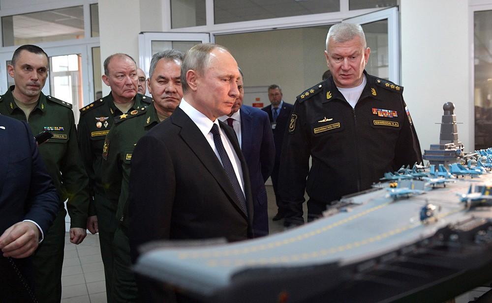 Владимир Путин осматривает экспозицию, посвященной перспективам развития ВМФ